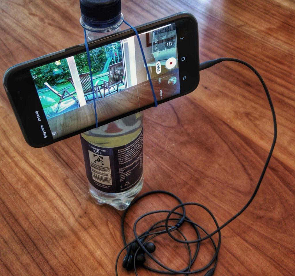 Bernhard Lill zeigt, wie man ein Stativ und eine Smartphone-Halterung selbst bastelt: mit einer Wasserflasche und einem Gummiband.